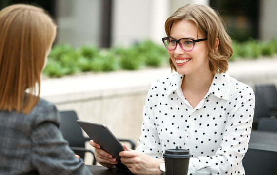 Smiling woman with digital tablet in hand discussing startup with business partner in outdoor cafe