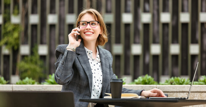 Smiling attractive businesswoman talking on mobile phone while waiting for partner or client outdoors