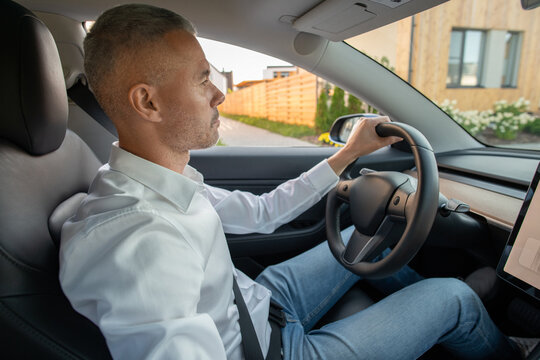Serious mature man in jeans and white shirt sitting by steering wheel while driving new electric car