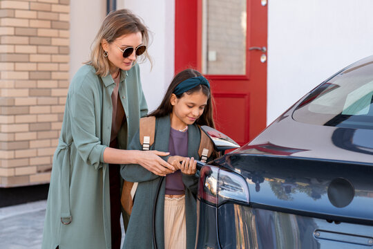Mother and daughter charging battery of electric car before driving to school