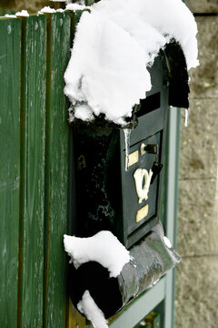 Snow covered old mailbox on wooden door