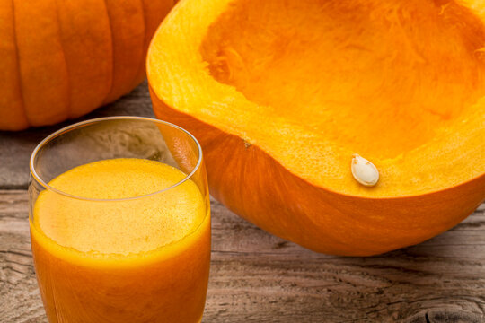 a glass of fresh pumpkin juice on a rustic wooden table with cut pumpkin and seeds