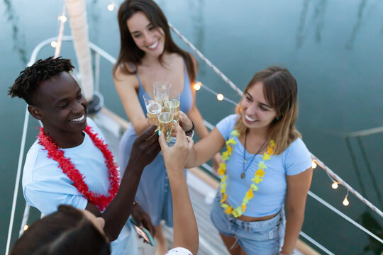 Multiracial group of young friends celebrating new year christmas on a boat - Four young multiethnic people and toasting with champagne and celebrating together - Focus on glasses