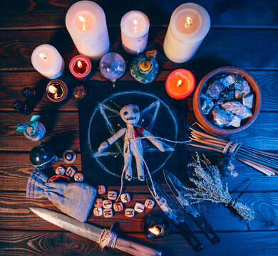 Voodoo doll on table in pentagramma and magical attributes, top view.