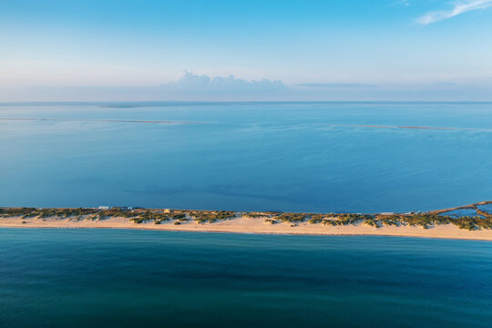 Long spit with beautiful sandy beach between sea and liman, aerial view from drone.