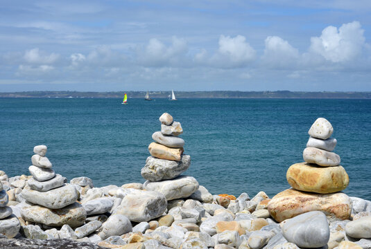 Zen stones concept at the ocean with sail boats in the background