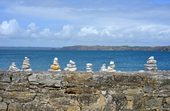 Stone wall with view at the atlantic ocean in Brittany, France with little stone symbols