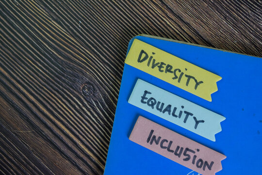 Diversity, Equality, Inclusion write on sticky notes isolated on Wooden Table.