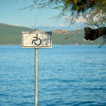 Sign for a handicapped accessible beach on the otherwise rocky coast of the Adriatic Sea near Krk in Croatia