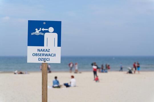 Sign on the beach of the Baltic Sea near Kołobrzeg with the inscription Order to observe children (Nakaz Obserwacji Dzieci)