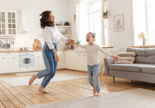 Mom and her daughter are dancing.