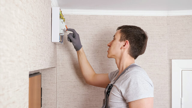 Professional electrician in jumpsuit presses levers on contemporary switchboard to fix above front door in entry room close side view