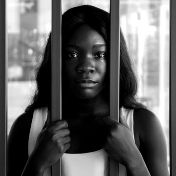 close-up of an african american woman with a sad look behind an iron bars, black and white image