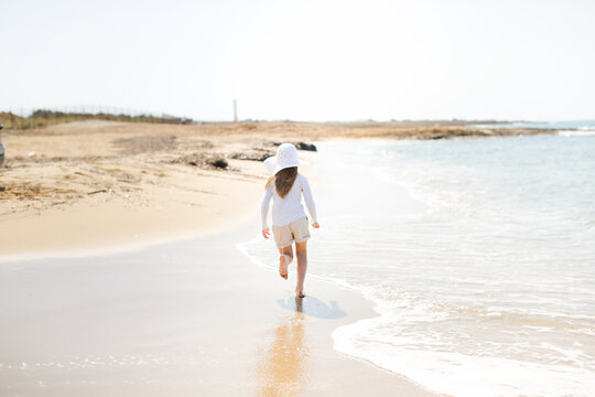 Cute caucasian child girl with long hair by sea. A child in hat and long sleeve with shorts, protection from sun, first spring sea, the beginning of sea season. Childhood and freedom, joy from sea