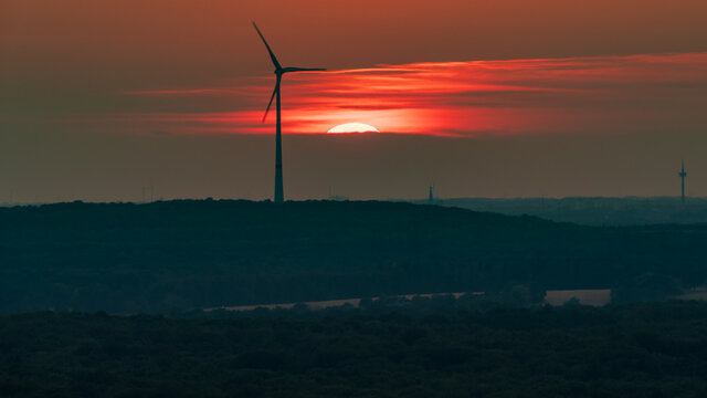 The setting sun and some wind turbines in the Ruhr Area, seen from the Halde Haniel, Bottrop, North Rhine-Westfalia, Germany