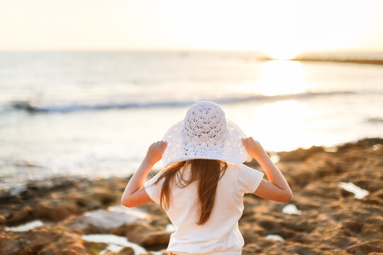 Cute caucasian child preteen girl with long hairs in a wicker white hat walking on the stones by the sea, sea trips, vacation and freedom, childhood by the sea