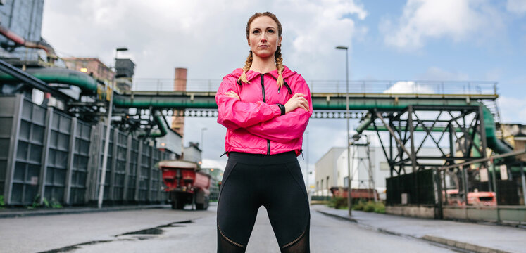 Sportswoman with crossed arms posing in front of a factory in an industrial zone