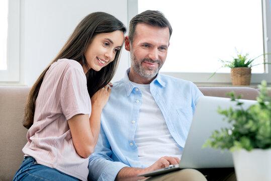 Couple using laptop, watching movie, browsing web