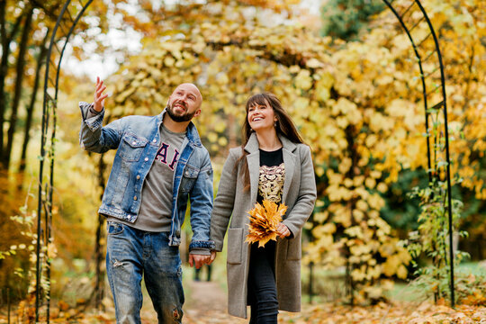 A young married couple walks through the autumn park, holding hands, a girl holds a bouquet of leaves in her hand. The concept of relationships and love