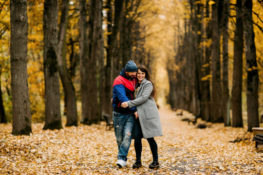 Two lovers walk along an alley in an autumn park and hug each other. Autumn, love, a romantic date