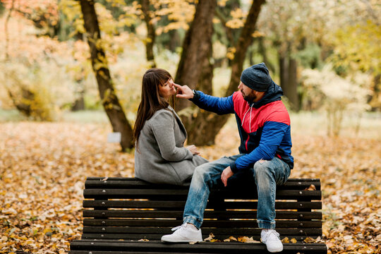 A young man is sitting on a bench in an autumn park with his beloved girlfriend and gently touches her nose with his finger. Romance, relationships, tenderness