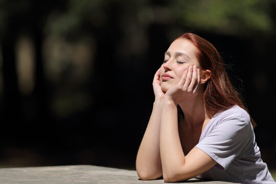 Woman with closed eyes relaxing a sunny day in a park