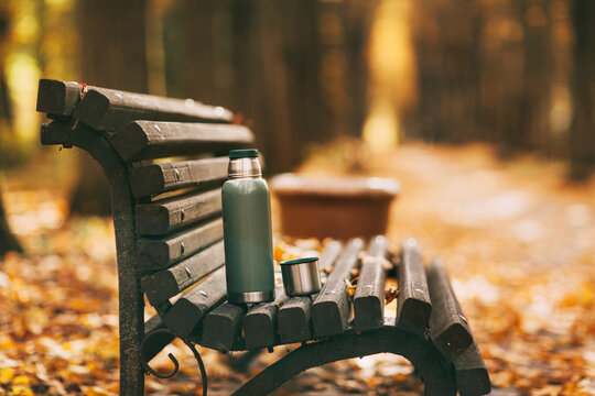 A tourist thermos with a cup stands on a bench in an autumn park