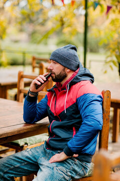 A young man using a mobile phone is sitting outdoors in a cafe or restaurant on an autumn day