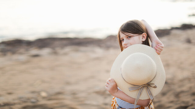 Cute caucasian child girl with long hair with a wicker hat by the sea, summer funny child portraits, children's emotions, happy stylish childhood