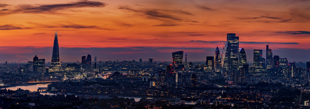 Wide panoramic view of the illuminated skyline of London, United Kingdom, during evening time with orange sky