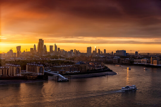 The skyline of London, United Kingdom, along the Thames river during a golden sunset with boat traffic