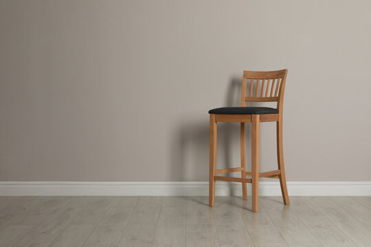Stylish bar stool near light grey wall indoors. Space for text