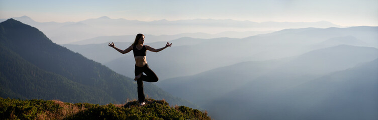 Fototapeta Panoramic view of fit young woman performing yoga pose on grassy hill with mountains and sky on background. Beautiful woman in sportswear practicing yoga outdoors. Copy space. obraz