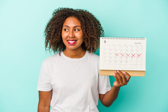 Young african american woman holding a calendar isolated on blue background looks aside smiling, cheerful and pleasant.
