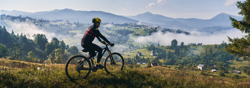 Man riding bicycle on grassy hill and looking at beautiful misty mountains. Male bicyclist enjoying panoramic view of majestic mountains during bicycle ride. Concept of sport, bicycling and nature.