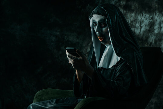 scary evil nun using her smartphone