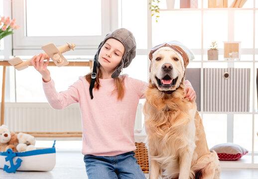 Little girl play in plane pilot with golden retriever dog