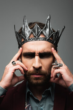 thoughtful and serious man in vampire king halloween crown touching head isolated on grey