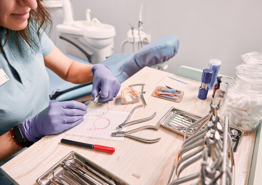 Dentist cutting braces wire while sitting at the table with orthodontic instruments. Woman orthodontist preparing wire for braces attachment. Concept of dentistry and orthodontic treatment.