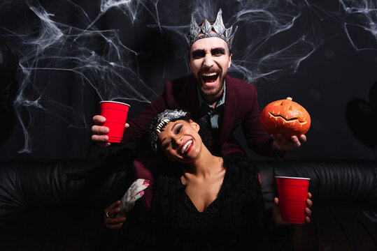 laughing man in vampire halloween costume with plastic cup and carved pumpkin near african american woman in wolf mask on black