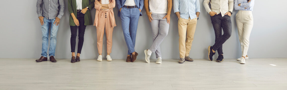 Group of successful confident business people in smart and casual wear standing in studio. Team of employees leaning on grey office wall. Cropped shot of people's legs in classic pants and jeans