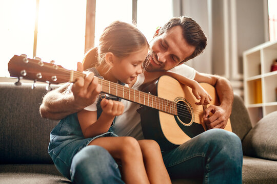 Happy dad teaches his cute daughter to play the guitar while sitting on the sofa in the living room at home. Happy Father's Day.