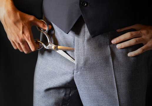 Cut the budget metaphor business concept. Scissor in trousers.