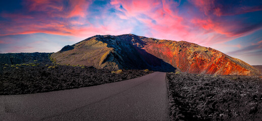 Timanfaya National Park, mountains of fire at Lanzarote, Canary Islands, Spain. Unique panoramic view of spectacular lava river flows from a huge volcano crater creates a lunar landscape on planet