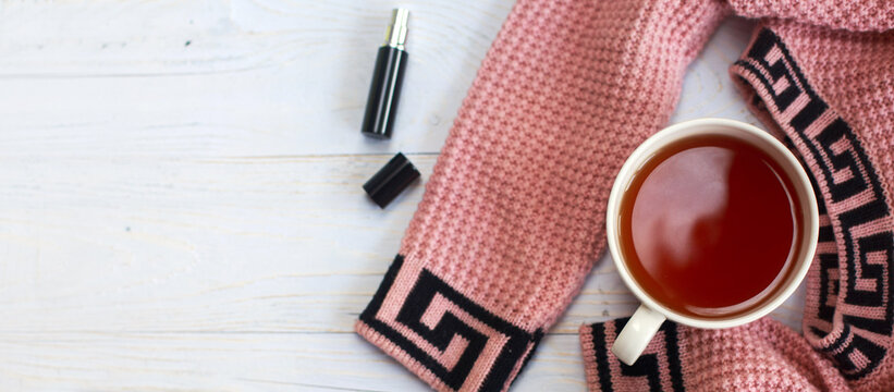 A cup of hot tea, knitted sweater, and perfume on wooden light table. banner. winter morning concept