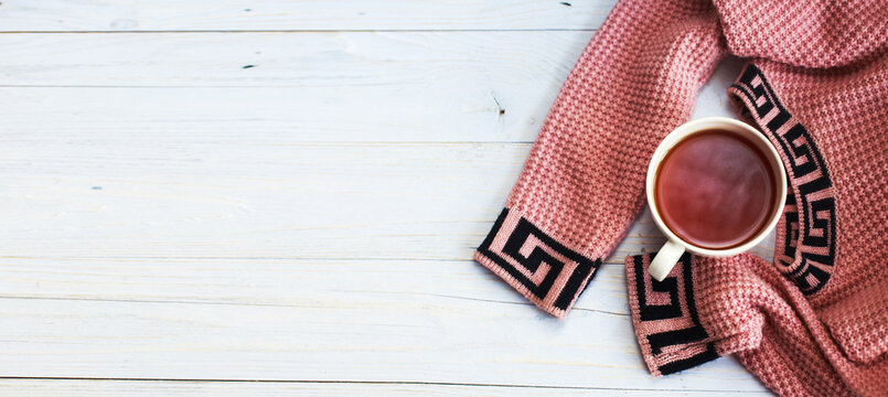 Cup of hot coffee with knitted sweater on wooden table, winter morning concept. banner