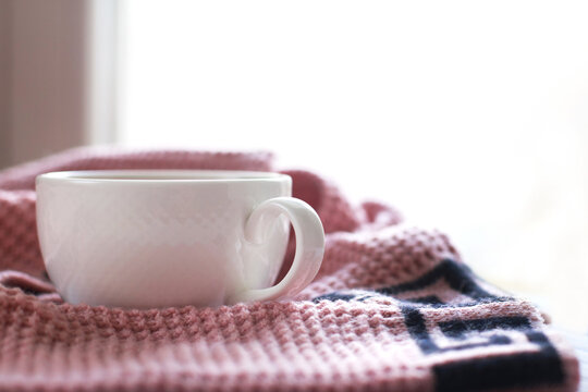 Cup of hot coffee with knitted sweater on wooden table near the window, winter morning concept