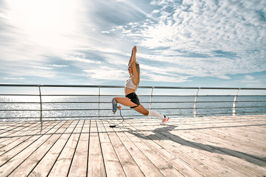 Life balance. Calm and sporty disabled athlete woman in sportswear with prosthetic leg standing in yoga pose on the bridge in front of the sea.
