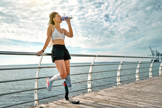 Full length of young disabled athlete woman with prosthetic leg standing on the bridge and drinking water from a bottle.