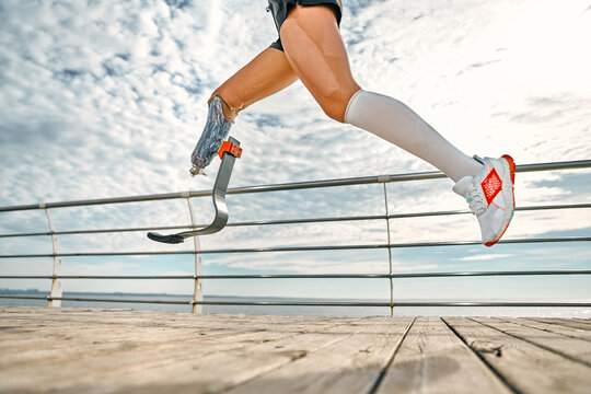 Life is in your hands. Cropped photo of disabled woman with bionic leg in sportswear is running on the bridge in the morning.